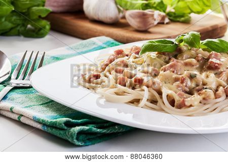 Spaghetti carbonara with bacon and basil on a plate poster