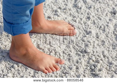 Close up of child feet on a tropical sandy beach