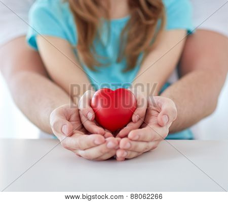 people, charity, family and advertisement concept - close up of father and girl holding red heart shape in cupped hands at home