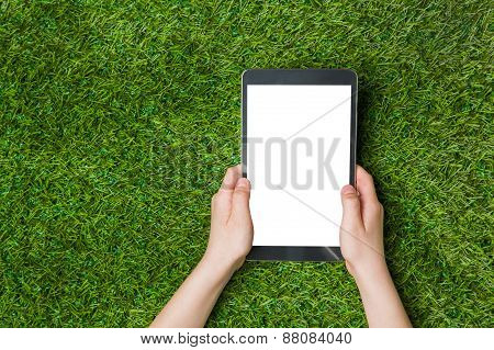 Child hand holding tablet pc. over green grass