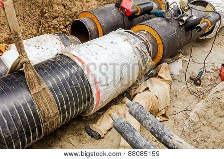Welder Is Working Under A Big Pipeline