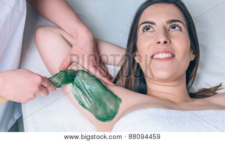 Beautician hands doing depilation armpit to beautiful woman with hot wax in a beauty salon poster