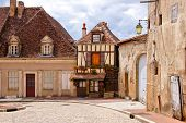 Quaint street in a town in Burgundy France with small timbered house poster