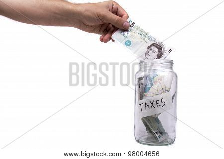 Placing money in a jar labeled Taxes