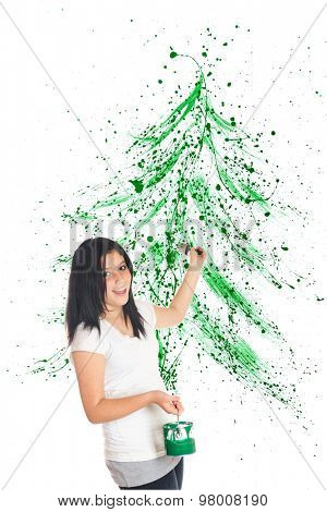An attractive preteen flinging green paint to create a splattered Christmas tree image behind her.  On a white background.