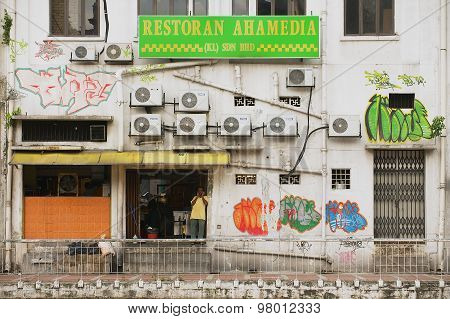 Man stands at the restaurant entrance at the backstreet in Kuala Lumpur, Malaysia.
