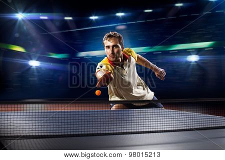 young sports man tennis player playing on black background with lights