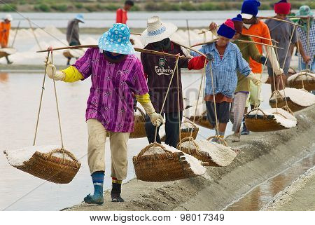 People carry salt at the salt farm in Huahin, Thailand.