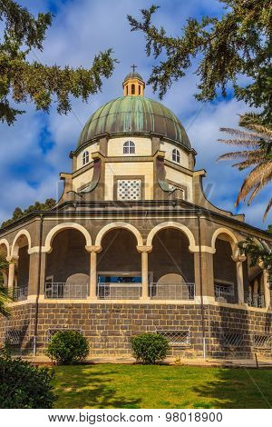 Church Sermon on the Mount - Mount of Beatitudes. The basilica is surrounded by a gallery with columns. Subtle shade of palms and cypresses poster