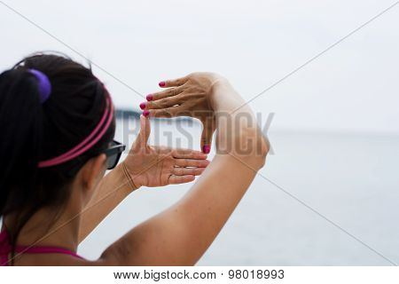 Woman Making Viewfinder From Hands