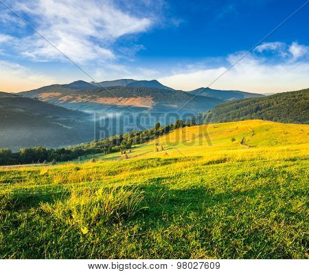 Haystacks In Agricultural Field In Mountain