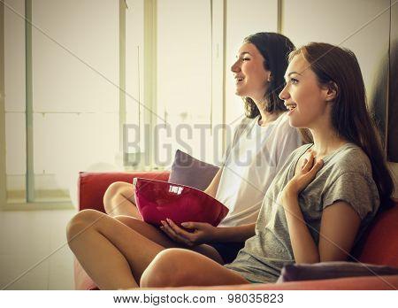 Girls sitting on the sofa enjoying a movie