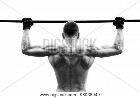 Muscle Man Making Pull-up On Horizontal Bar Against The Sky