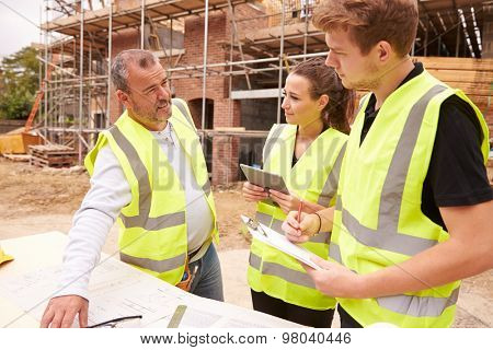 Builder On Building Site Discussing Work With Apprentices