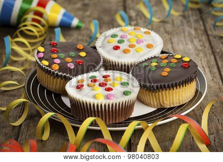 Cupcakes with chocolate icing and smarties on a plate surrounded by streamers