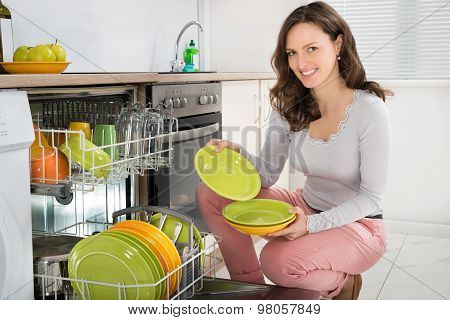 Woman Arranging Plates In Dishwasher