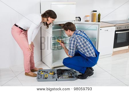 Housewife Looking At Worker Repairing Refrigerator