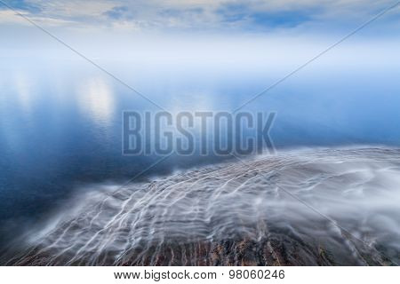 Water flows over the sandstone ledges of Michigan's northern coast and into Lake Superior with a cloud-draped horizon. Elliot Falls is in Pictured Rocks National Lakeshore near Munising Michigan. poster