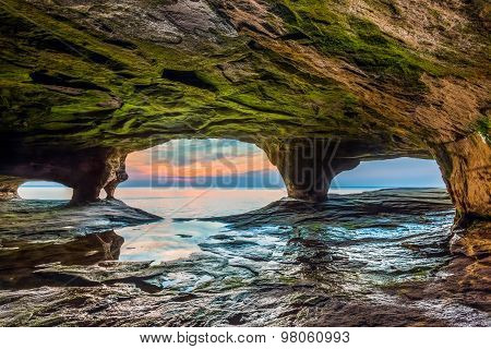 A colorful sunset is viewed through the portals of a Lake Superior sea cave on Michigan's northern coast. poster