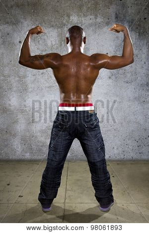 Fit black man in hip hop style clothing flexing back muscles poster