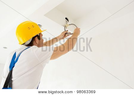 repair, renovation, electricity and people concept - close up of builder or electrician running wires indoors