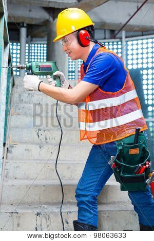 Asian Indonesian builder or worker drilling with a machine or drill, ear protection and hardhat or helmet  in a wall of a tower building or construction site poster
