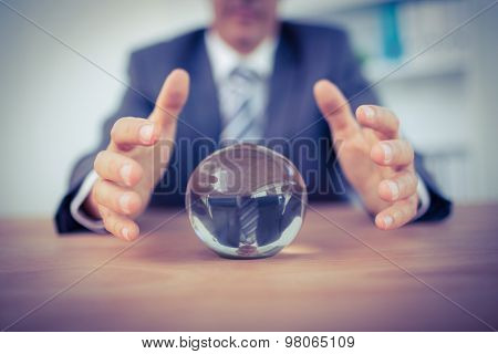 Businessman forecasting a crystal ball in the office poster