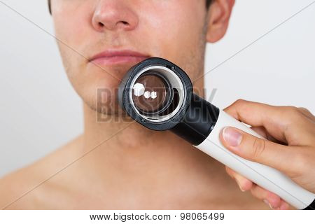 Person Hands Checking Man Face With Dermatoscope