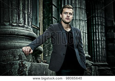 Handsome elegant man posing on a city street. Fashion shot. Business man outdoor.