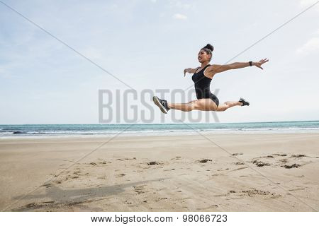 Fit woman leaping on the sand at the beach