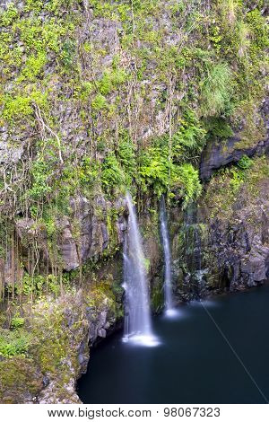 Surrounded by lush vegetation, a small waterfall in Hilo Hawaii forms cascading flows into a natural pool.