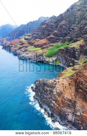 An aerial view of the Na Pali coast in Kauai Hawaii during a vibrant, sunny day shows the rich colors of the scenic coastline.