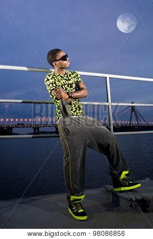 rapper on quay with bottle of champagne in the bright of the moon