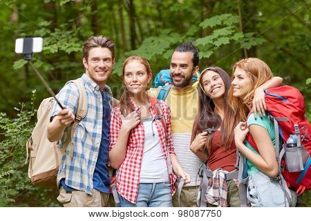 technology, travel, tourism, hike and people concept - group of smiling friends walking with backpacks taking picture by smartphone on selfie stick in woods