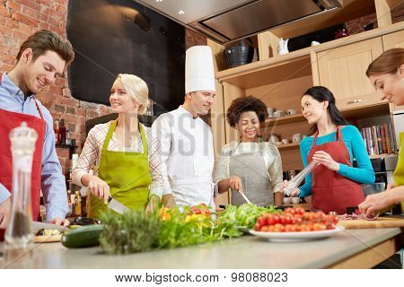 cooking class, culinary, food and people concept - happy group of friends with male chef cook cooking and talking in kitchen