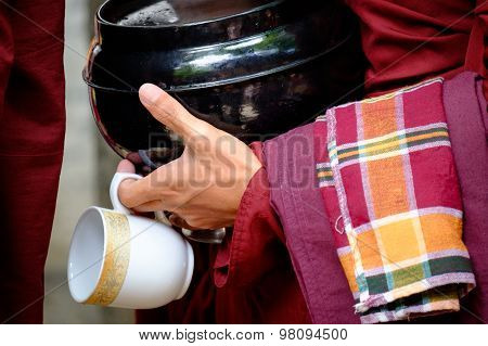 Colorful Details Of Buddhist Monk Hands Holding A Bowl And Cup