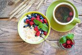 Healthy breakfast - oatmeal with berries and a cup of green tea poster