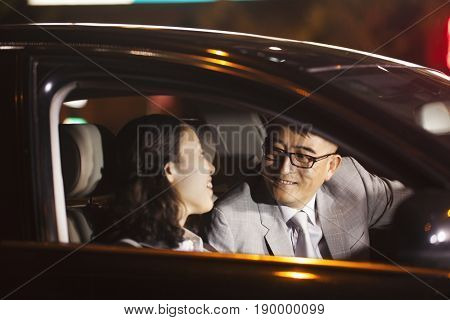 Chinese business people talking in car