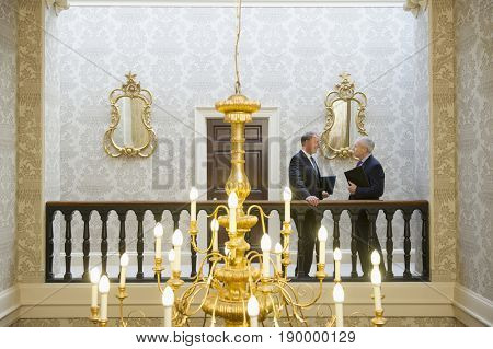 Caucasian businessmen talking in ornate hallway