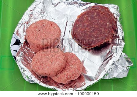 Two Types Of Burger, Traditional Beefburgers And Unusual Zebra Burgers, On Tin Foil Waiting To Be Co