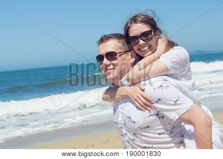 Young romantic couple spending vacation or weekend on the beach, enjoying each other, being silly and laughing, having great time together.