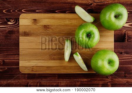Green apples with slices and bamboo cutting board on brown plank top view copy space.