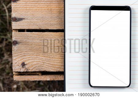 Notepad and bezel less smartphone with blank screen. Ready for mobile application mockup.