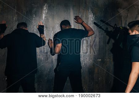 Arrested bandits near the wall at night. Security, people outside the law, megalopolis night life, drug trafficking, violence and social problems of society concept