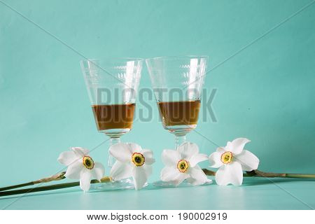 Two glasses of cognac or brandy and white daffodils on a neutral background Romantic gift.