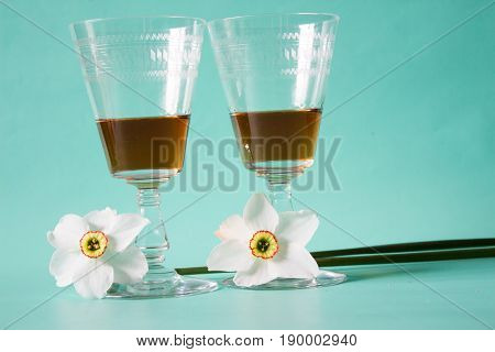 Two glasses. bottle of cognac or brandy and white daffodils on a neutral background Romantic gift.