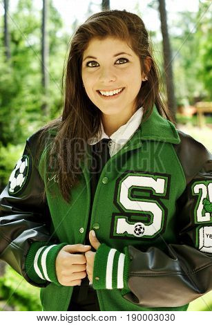 High School Graduate poses in a park for her graduation pictures showing her soccer jacket with her surname on