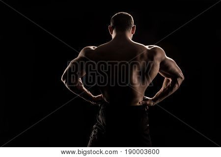 Back View Of Young Shirtless Athlete Flexing Back Muscles