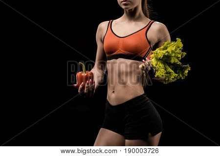Cropped Shot Of Sportswoman Holding Bell Pepper And Lettuce Salad Leaves