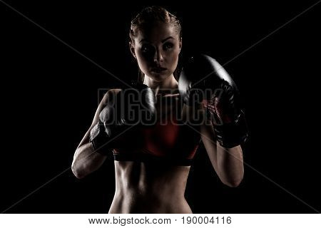 Caucasian Muscular Sportswoman Exercising In Boxing Gloves Isolated On Black